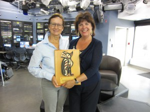 Daphne Goode of Shaw TV South Vancouver Island receives Swiftsure's 2014 sponsor plaque from Charlotte Gann.